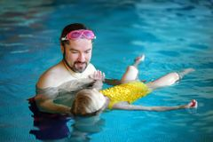 Padre feliz que enseña a su pequeña hija a nadar Niño feliz activo que aprende nadar Imagen de archivo