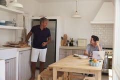 Padre feliz que habla con su hijo, haciendo la preparación en cocina Imágenes de archivo libres de regalías