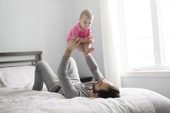 Padre feliz que juega con el bebé adorable en dormitorio foto de archivo