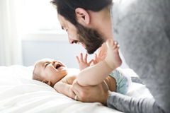 Padre feliz que juega con el bebé adorable en dormitorio Fotografía de archivo libre de regalías