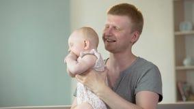 Padre feliz que juega con el pequeño bebé lindo, disfrutando de paternidad consciente almacen de metraje de vídeo