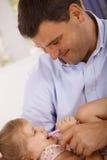 Padre feliz que juega con la pequeña sonrisa de la hija Foto de archivo