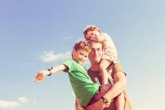 Padre feliz que juega con los niños al aire libre Imágenes de archivo libres de regalías