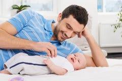 Padre feliz que juega con un bebé Imagen de archivo libre de regalías