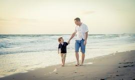 Padre feliz que lleva a cabo la mano del pequeño hijo que camina junto en la playa con descalzo Imagenes de archivo