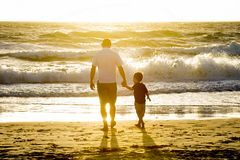 Padre feliz que lleva a cabo la mano del pequeño hijo que camina junto en la playa con descalzo Foto de archivo