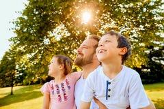 Padre feliz que pasa tiempo con los niños en parque Foto de archivo libre de regalías