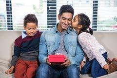 Padre feliz que recibe un regalo de sus niños imagenes de archivo