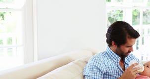 Padre feliz que se sienta en un sofá que cría con biberón a su bebé almacen de metraje de vídeo