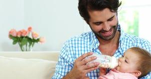 Padre feliz que se sienta en un sofá y que cría con biberón a su bebé almacen de video