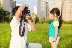 Padre feliz que toma la imagen con la niña en el parque de la ciudad Imagen de archivo libre de regalías