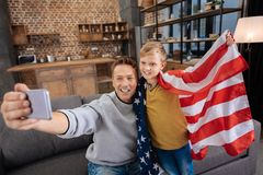 Padre feliz que toma selfies con el hijo en bandera de los E.E.U.U. Foto de archivo libre de regalías