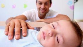 Padre feliz que vigila hijo del bebé en pesebre almacen de metraje de vídeo