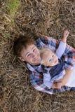 Padre feliz y bebé que se relajan en la granja imágenes de archivo libres de regalías