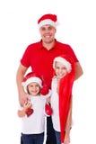 Padre feliz y dos hijas en la risa de los sombreros de santa foto de archivo