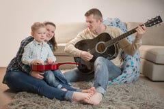 Padre feliz y familia que tocan las guitarras en casa Fotografía de archivo
