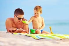 Padre feliz y niño que juegan en arena en la playa Foto de archivo libre de regalías
