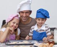 Padre feliz y niños que cuecen al horno las galletas juntas Foto de archivo libre de regalías
