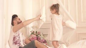 Padre feliz y pequeña hija que tienen una lucha de almohada en cama almacen de video