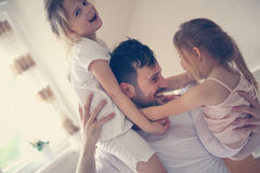 Padre feliz y pequeñas hijas que pasan tiempo en casa Imagen de archivo