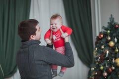 Padre feliz y pequeño hijo que juegan y que se divierten en casa cerca del árbol de navidad Fotos de archivo libres de regalías
