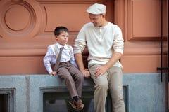 Padre feliz y pequeño hijo que se divierten en ciudad Foto de archivo libre de regalías
