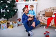 Padre feliz y su hijo en casa cerca de un árbol de navidad con un regalo fotografía de archivo