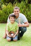 Padre feliz y su hijo que juegan a béisbol Imagen de archivo libre de regalías