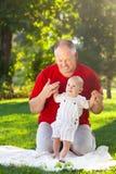 Padre feliz y su hijo que juegan en parque junto Portr al aire libre Foto de archivo libre de regalías