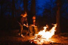 Padre feliz y su hijo que se sientan afuera delante de un fuego y que miran el fuego la noche foto de archivo
