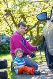 Padre feliz y su muchacho del niño que reparan el coche y que cambian w Fotografía de archivo libre de regalías