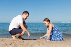 Padre feliz y su pequeña hija en la playa Imagen de archivo libre de regalías