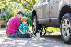 Padre feliz y su pequeño niño pequeño que reparan el coche y Changi Imágenes de archivo libres de regalías