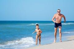 Padre feliz y su pequeño sol que corren en la playa Foto de archivo libre de regalías