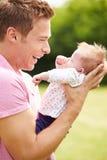 Padre fiero Holding Baby Daughter in giardino Fotografia Stock Libera da Diritti