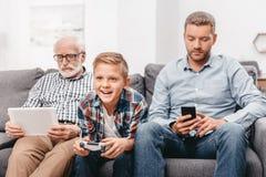 Padre, figlio e nonno sedentesi insieme sullo strato in salone facendo uso di vario immagini stock