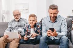 Padre, figlio e nonno sedentesi insieme sullo strato in salone facendo uso di vario fotografia stock libera da diritti