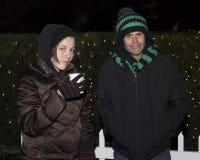 Padre gruñón e hija que se colocan en el frío delante de arbustos con las luces de la Navidad Fotografía de archivo