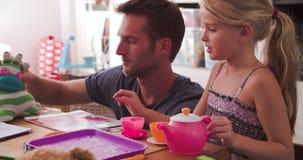 Padre Having Tea Party con il derivato ed i giocattoli in camera da letto archivi video