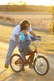 Padre Helping que su hijo aprende montar su bici en Sunny Spring Ev Fotografía de archivo libre de regalías