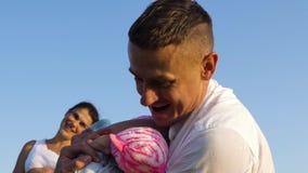 Padre hermoso joven que abraza la hija del niño y la observación embarazada de la madre metrajes