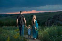 Padre, hija y madre caminando al aire libre Foto de archivo