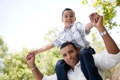Padre hispánico e hijo que se divierten en el parque Imágenes de archivo libres de regalías