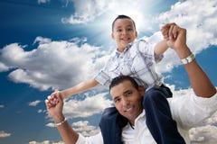 Padre hispánico e hijo que se divierten sobre las nubes Fotos de archivo libres de regalías