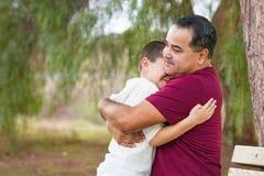 Padre hispánico Hugging His Son de la raza mixta en el parque foto de archivo