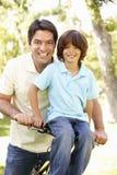 Padre hispánico joven And Son Cycling en parque imagen de archivo libre de regalías