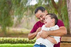 Padre hispánico Tickling His Son de la raza mixta en el parque fotos de archivo