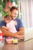 Padre Holding Baby And che produce spuntino mentre per mezzo del computer portatile Fotografie Stock Libere da Diritti