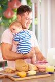 Padre Holding Baby And che produce spuntino mentre per mezzo del computer portatile Immagine Stock