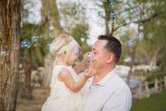 Padre Holding Baby Girl que disfruta de burbujas afuera en el parque Fotografía de archivo